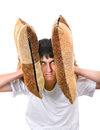 Displeased teenager with cushion covering his ears isolated on the white background Royalty Free Stock Images