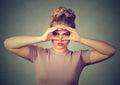 Displeased upset woman looking through fingers like binoculars Royalty Free Stock Photo