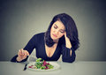 Displeased woman eating green leaf lettuce tired of diet restrictions