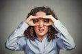 Displeased woman looking through fingers like binoculars Royalty Free Stock Photo