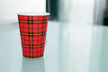 Disposable coffee cup on the glass table Royalty Free Stock Photos