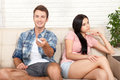Dissapointed beautiful brunette woman in quarrel with her boyfriend. Indifferent man watching TV. Royalty Free Stock Photo