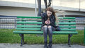 Dissapointed girl with long blonde hair in leather jacket straightens  use gadget sitting on the bench in the wind Royalty Free Stock Photo