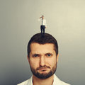 Dissatisfied man with small man unhappy on the head Stock Images