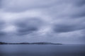 Distant islands cloudy evening by the sea with Royalty Free Stock Photo