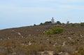 A distant lighthouse on a hilltop barren land leading to santa pola spain s costa blanca coast Royalty Free Stock Photo