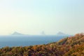 Distant rocks view to rock islands in a haze there is motley forest in the foreground and boats in the sea Royalty Free Stock Photo