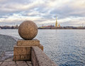 A distant view of Peter and Paul Fortress from behind the granite ball of The Spit of Vasilievsky island. Royalty Free Stock Photo