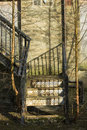 Disused metal steps fire escape to the rear of a derelict building casting shadows on the stone wall with tress and shrubs growing Stock Photography