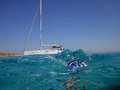 Diver and boat on sea a in the clear blue water sailing anchored in the Royalty Free Stock Photo