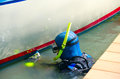 Diver cleaning boat hull maintenance work at dock scuba with snorkel and aqualung tank is a with a scrubbing pad removing all Stock Photo