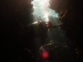 Diver exploring cave lit by shafts of sunlight while caverns in the southern red sea Royalty Free Stock Photography