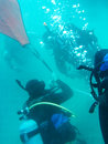 Divers working underwater four attaching a lift bag to an item Royalty Free Stock Photo