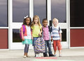 Diverse group of kids going to school young elementary age standing in front their getting ready go inside Royalty Free Stock Photos