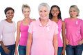 Diverse group of women wearing pink tops and breast cancer ribbons on white background Stock Photography