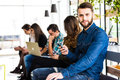 Diversity people connection digital devices browsing concept. Friends. Focus on first bearded smile man. Royalty Free Stock Photo
