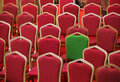 Diversity or unique concept green chair in a group of red ones different Royalty Free Stock Image