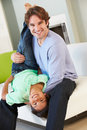 Divertimento de and son having do pai em sofa together Imagem de Stock Royalty Free