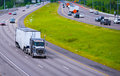 Divided Highway Curve large semi truck with bulk trailer Royalty Free Stock Photo