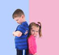Divided upset children back to back two are standing on a pink and blue background and unhappy for a discipline or gender concept Stock Images