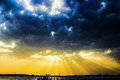 Divine sunset with sun rays breaching the dark clouds Royalty Free Stock Photos