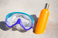 Diving mask and suntan lotion bottle on sandy beach close up of Royalty Free Stock Images