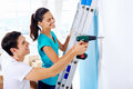 Diy couple drilling in wall doing at new home after moving in together Stock Photography
