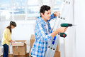 Diy couple drilling in wall doing at new home after moving in together Stock Images