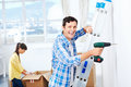Diy couple drilling in wall doing at new home after moving in together Royalty Free Stock Photo