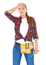 Diy handy woman with a dazed expression standing her hand raised to her forehead in knotted plaid shirt tool belt Royalty Free Stock Images