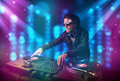 Dj mixing music in a club with blue and purple lights young Royalty Free Stock Photos