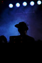 Dj silhouette mixing live at a concert blue light in the background Stock Photo