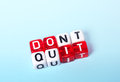 Do it dont quit written on red and white dices on blue background Stock Photos