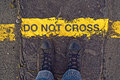 Do not cross the line on the border male sneakers asphalt road with yellow and title concept danger or warning sign Royalty Free Stock Photos