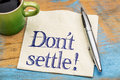 Do not settle reminder on napkin handwriting a with a cup of coffee Royalty Free Stock Photography
