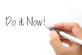 Do it now concept with hand holding pen against white background Royalty Free Stock Image