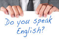 Do you speak english a man wearing a suit holding a signboard with the sentence written on it Stock Photos