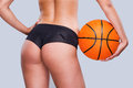 Do you want to play close up of beautiful young woman with perfect buttocks holding basketball ball while standing against grey Stock Image