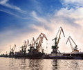Dock cranes cargo in the by the water over blue sky Stock Image