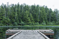 Dock on heart lake small wooden quiet backdropped by dense green pine forest cloudy summer day in southeast alaska Stock Images