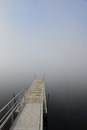Dock in lake with heavy fog boat extending into foggy Royalty Free Stock Images