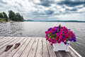 A dock on the lake with sandals cottage scene of planter of petunias and pair of there is boat in distance Stock Photo