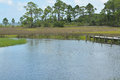 A dock in a stream flowing to St George Sound near Carrabelle, Florida Royalty Free Stock Photo