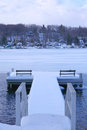 Dockside view of lake in winter benches on snow covered dock provide scenic landscape frozen Stock Image