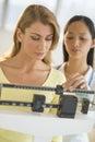Docteur weighing female patient sur l échelle de poids Photo stock
