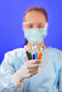 Doctor analyzing medical test tubes on blue Royalty Free Stock Photo