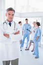 Doctor with arms folded in front of his medical team Royalty Free Stock Photo