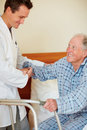 Doctor assisting an elderly patient onto a walker Stock Photography