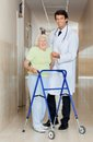 Doctor assisting an old woman with her walker full length portrait of a young male senior women Stock Photo