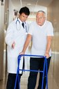 Doctor assisting senior man on a walker helping patient walk down hallway using zimmer frame Royalty Free Stock Photos